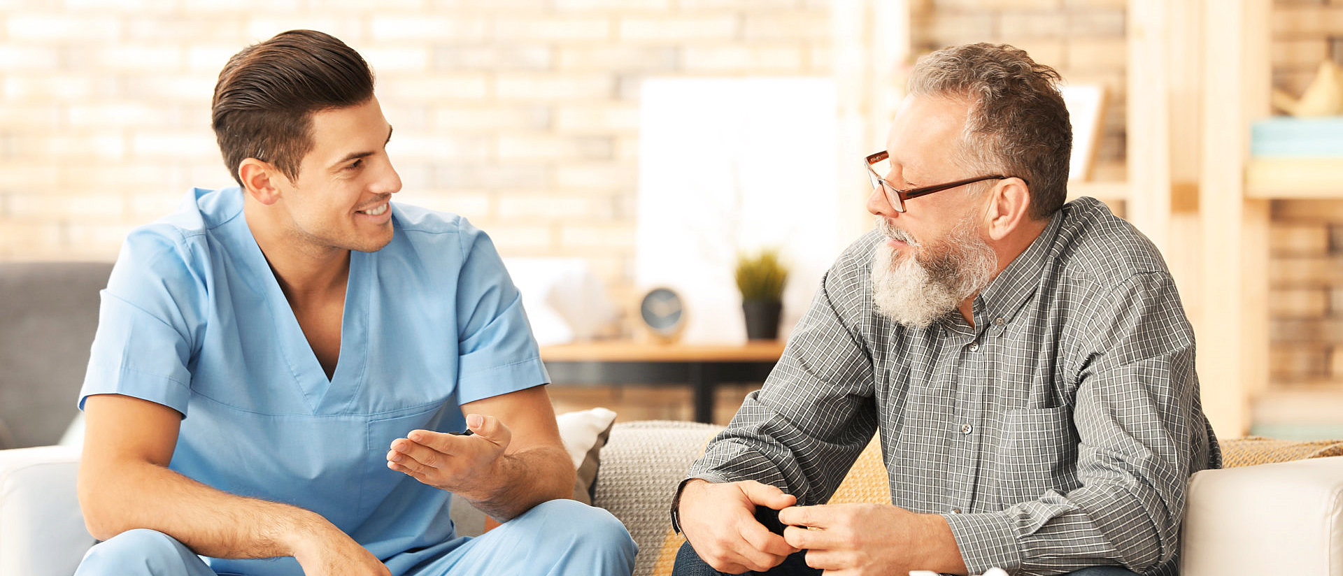 senior man and a male caregiver talking